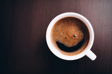 Cup of coffee with foam, smile face, on desk isolated