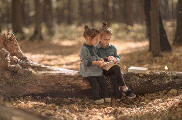 two beautiful little girls reading books in the autumn forest , sitting on a log. The concept of education and friendship.
